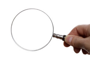 Hand holding a magnifying glass with blank space for design or text